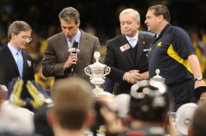 Allstate President Tom Wilson (far left) helps present Michigan coach Brady Hoke (far right) accepted the trophy for the Wolverines' victory in the 2012 Sugar Bowl.