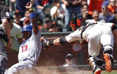 Dodgers shortstop Hanley Ramirez slides for the score at home plate as Giants catcher Buster Posey tries to tag him out. (AP Photo)